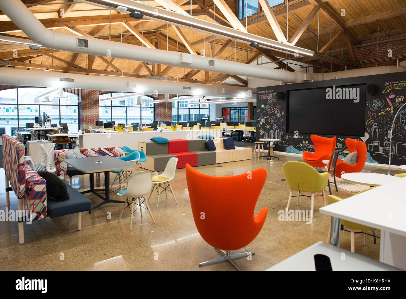 Trendy modern open concept loft office space with big windows, natural light and a layout to encourage collaboration, - Stock Image