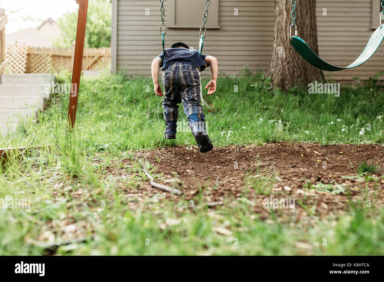 Rear view of playful boy swinging at playground - Stock Image