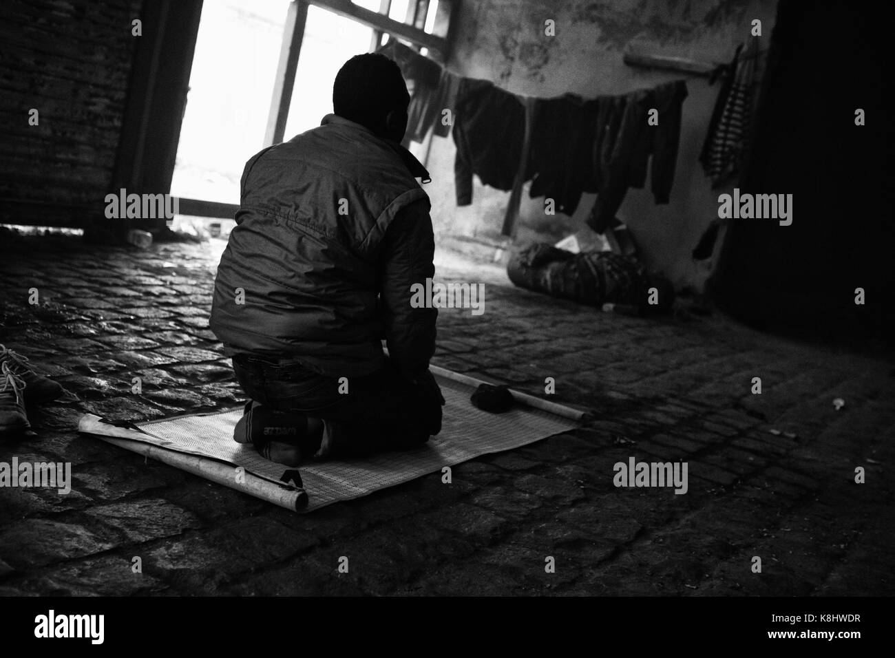 A Sudanese asylum seeker prays toward Mecca in an illegal, abandoned warehouse called 'Africa House' in - Stock Image