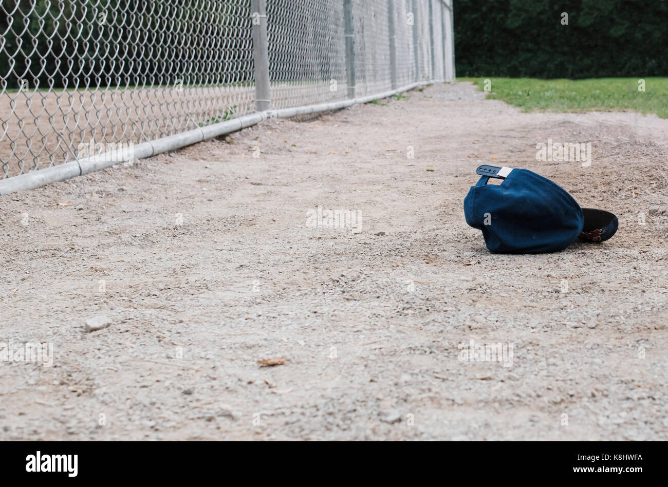 Cap on playground by chainlink fence - Stock Image