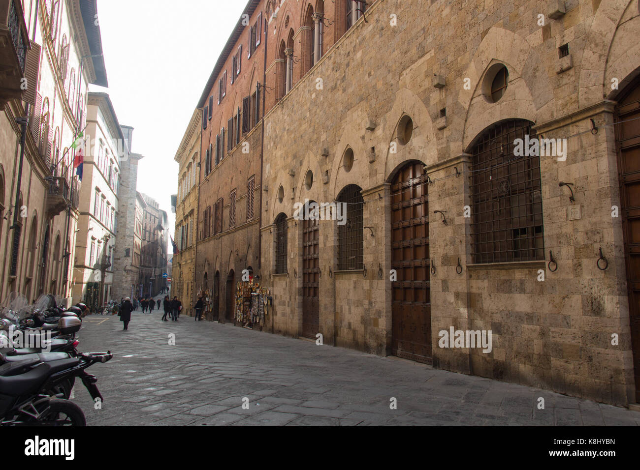 Italy, Siena - December 26 2016: the street view of Siena with typical medieval buildings, people, motorbikes on - Stock Image