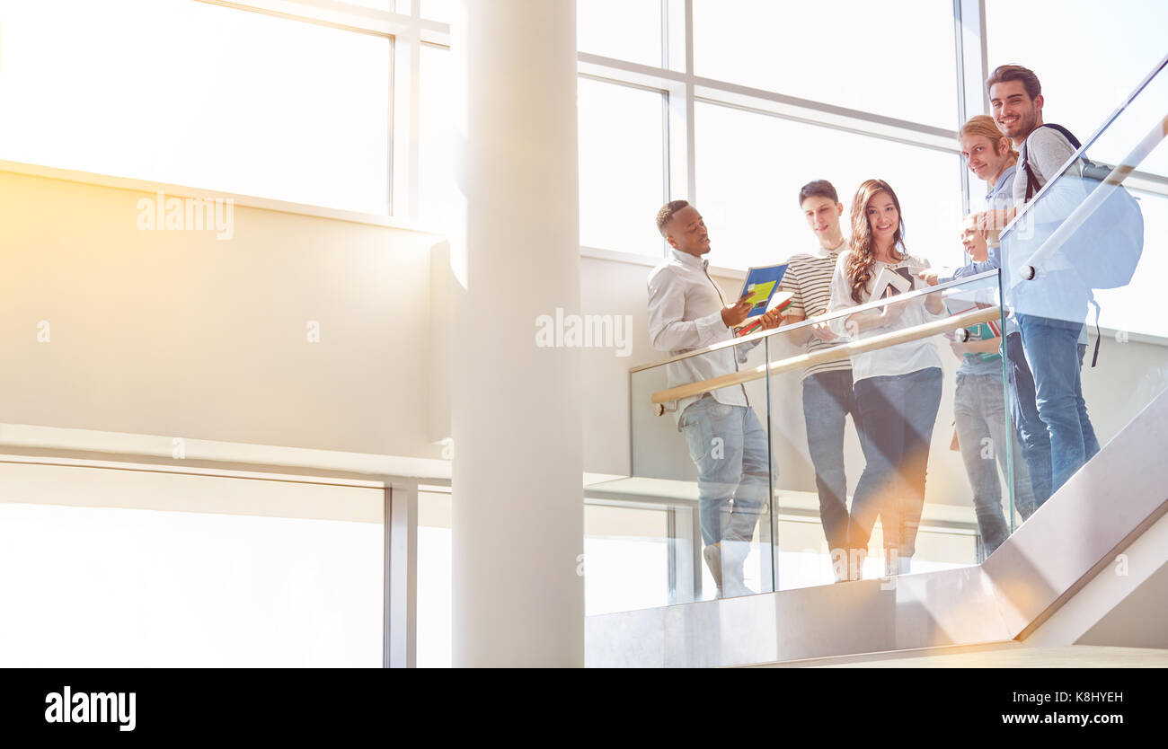 Students as friends have break in university staircase - Stock Image