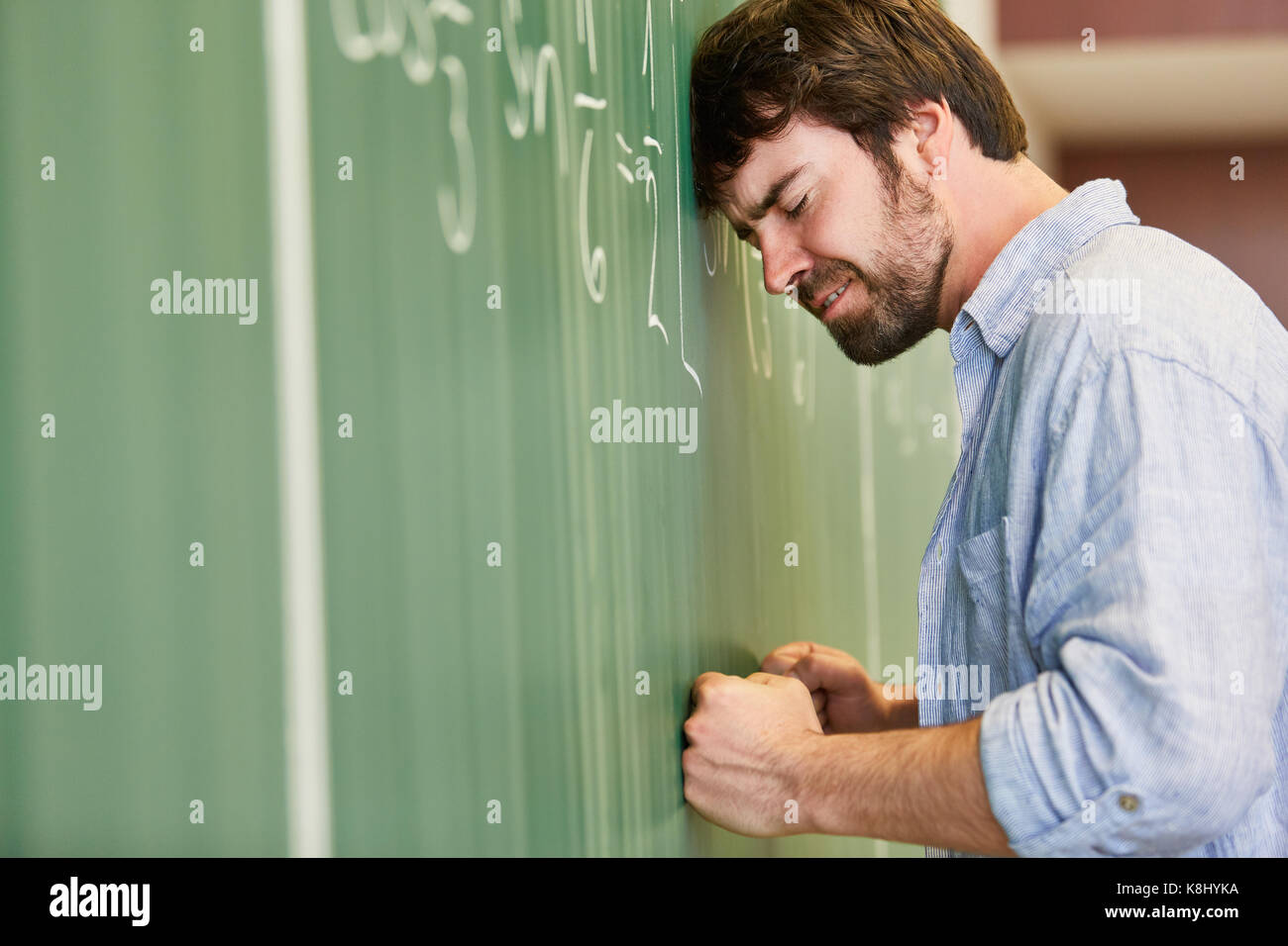 Student calculating math problem on chalkboarf with frustration ...