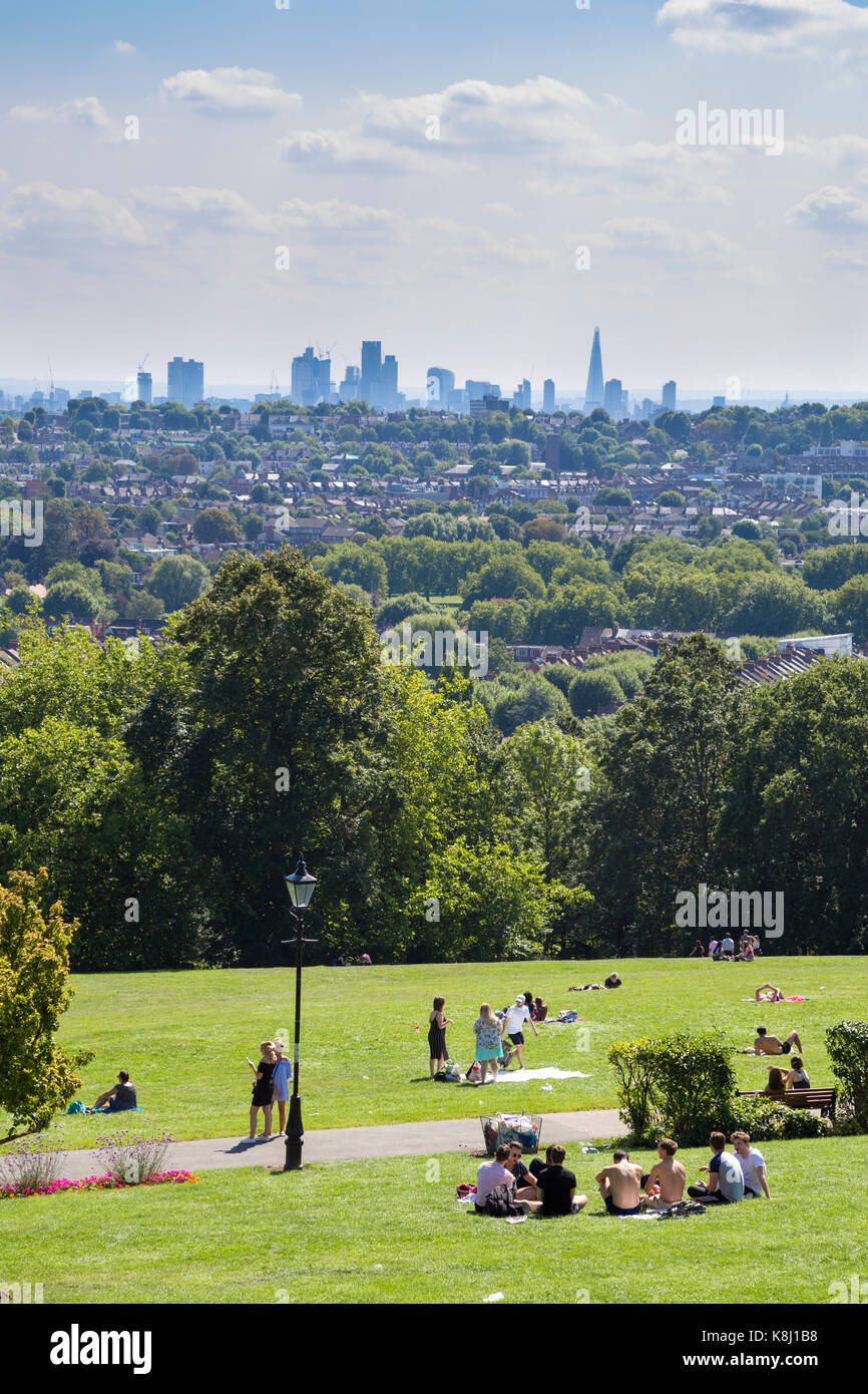 People walking and picnicking at Alexandra Palace Park with views over North London and central London skyline, - Stock Image