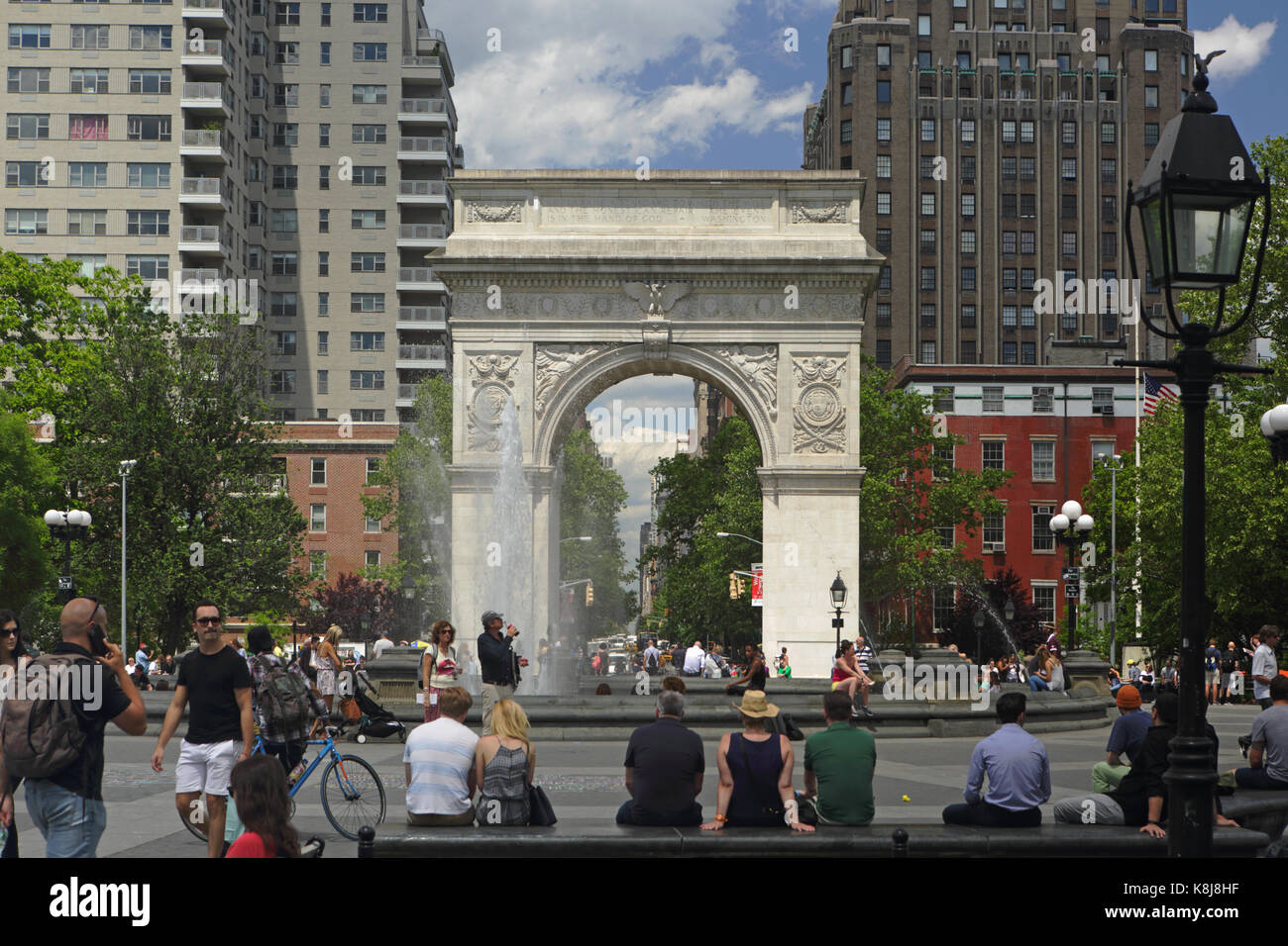 New York, NY, USA - June 1, 2017: Tourists and New York locals alike enjoy a sunny day in Washington Square Park - Stock Image