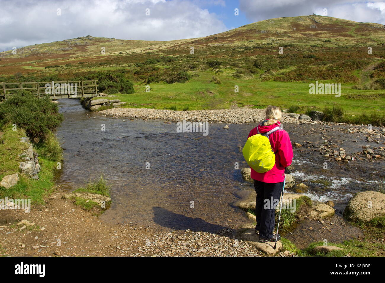 Female in red on the River Lyd with wooden bridge and stepping stones Dartmoor National Park Lydford Devon England - Stock Image