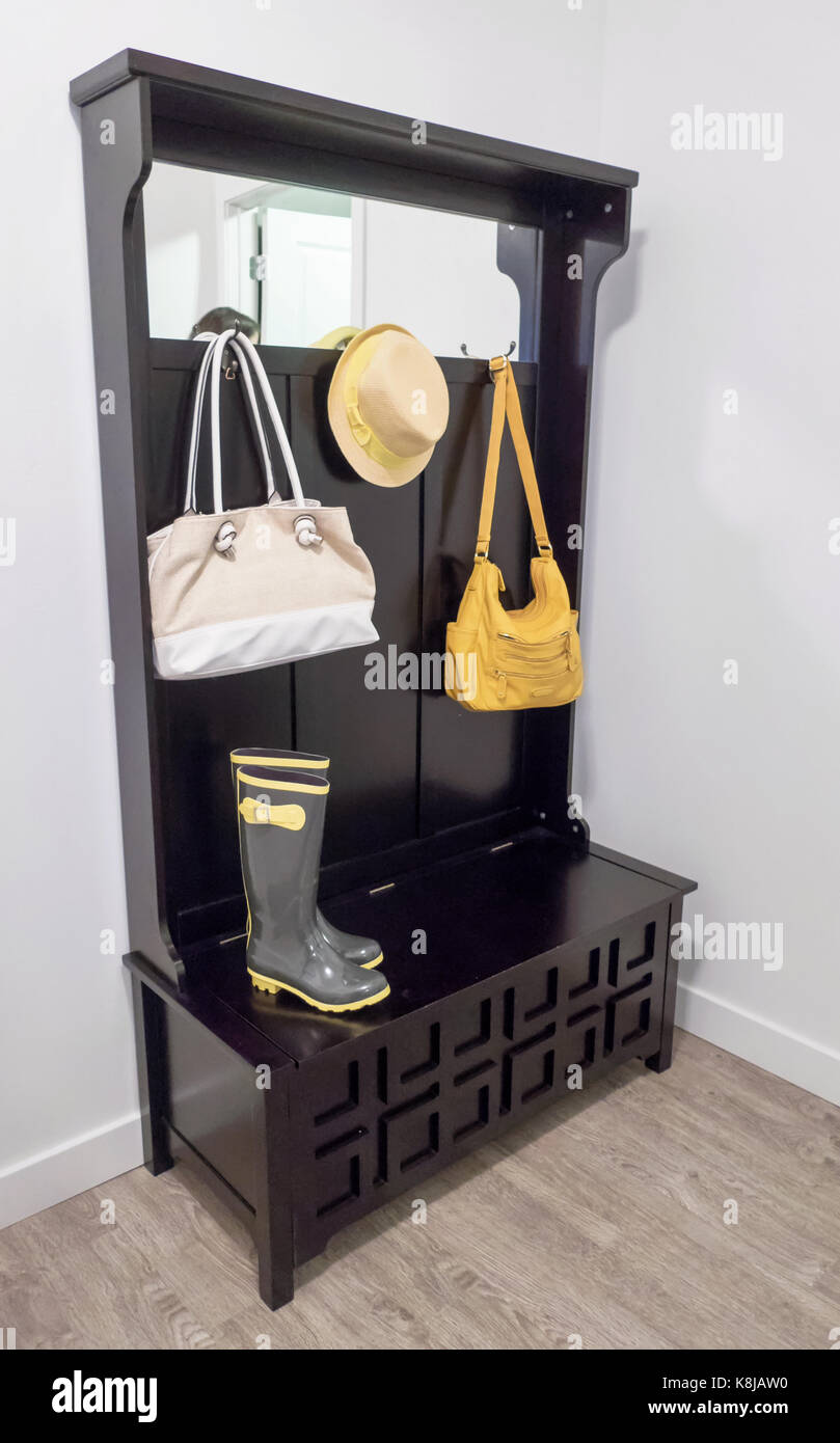 A small bench with mud boots, purses and a hat. - Stock Image