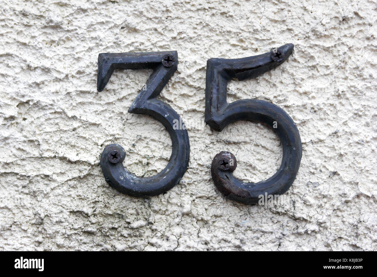 The number 35 in metal screwed on a wall - Stock Image