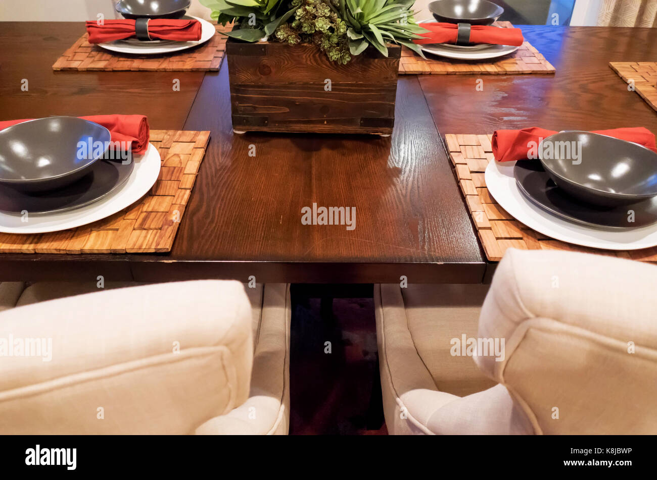 A warm dining room with gray bowls and tan chairs at a brown table. - Stock Image