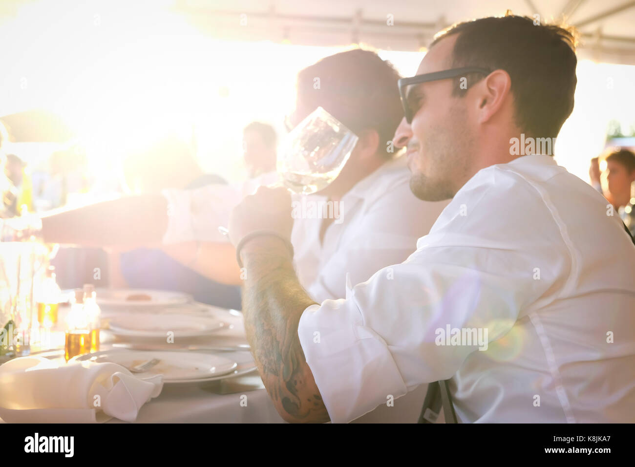 Outdoor shot of handsome young man drinking wine at a summer party with a friend - Stock Image