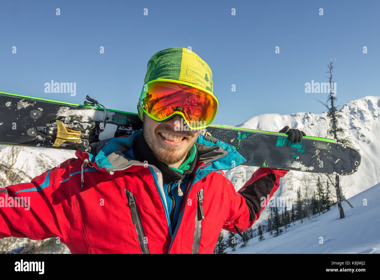 Portrait young man ski goggles holding ski in the mountains. - Stock Image