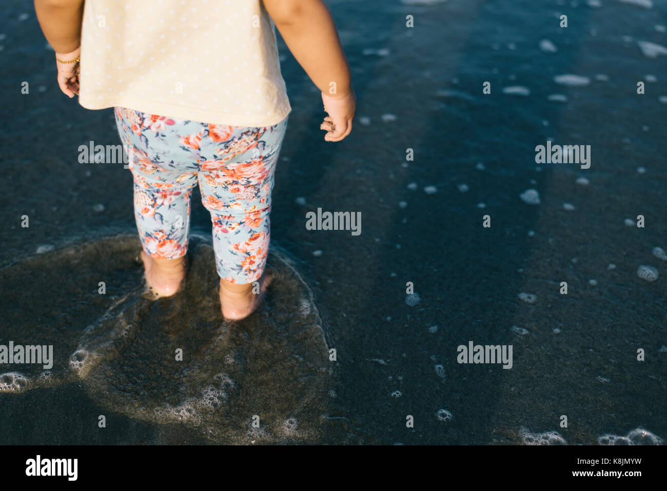 baby playing with waves on the beach.growth and learning concept.family and parenting concept - Stock Image