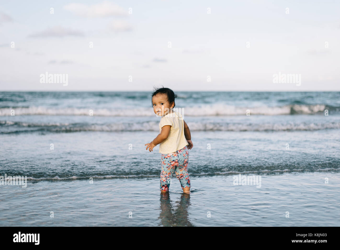 baby or infant playing beach waves for the first time making  curious face.learning concept.parenting concept - Stock Image