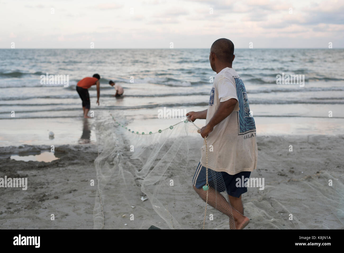 fishermen are fishing using fishing net by the beach in the evening - Stock Image