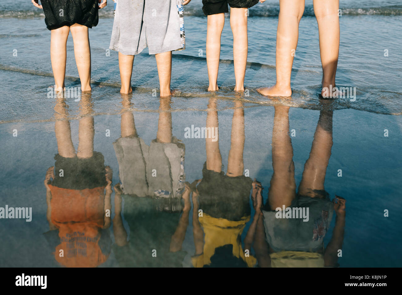 reflection of kids standing at the beach in the evening.travel and family concept,friendship and togetherness concept - Stock Image