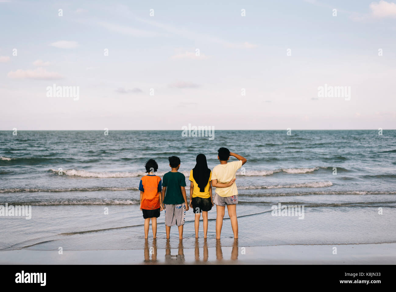kids standing at the beach enjoying sea views.friendship concept.family concept.holiday concept - Stock Image