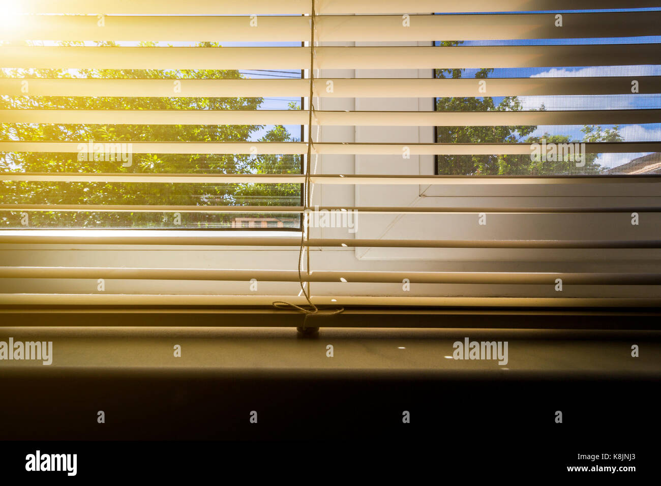 The summer sun shines through the blinds of the window of a rural house. Stock Photo