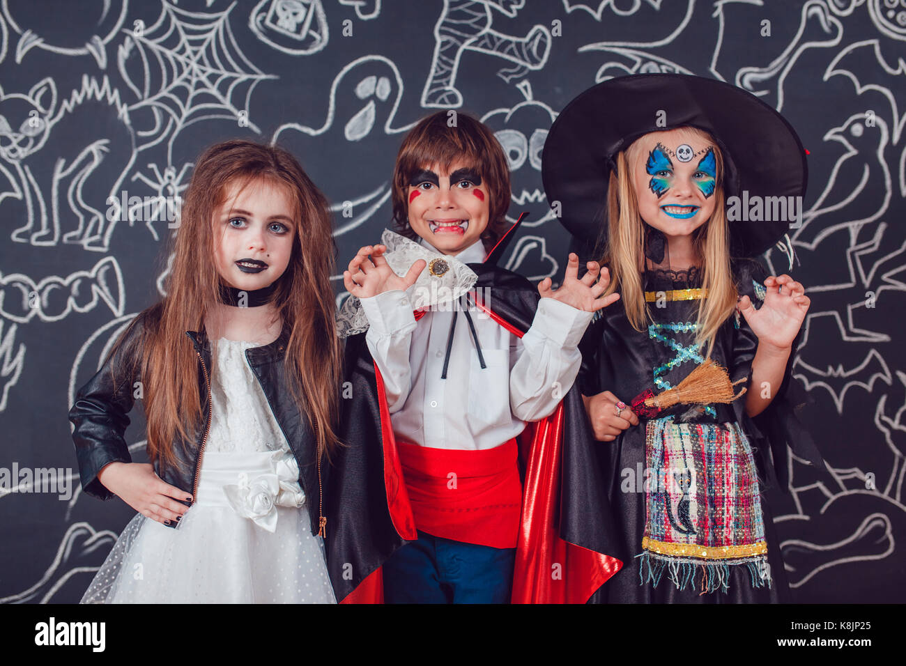 Children In Scary Halloween Costumes Stand Against A Wall With Stock Photo Alamy