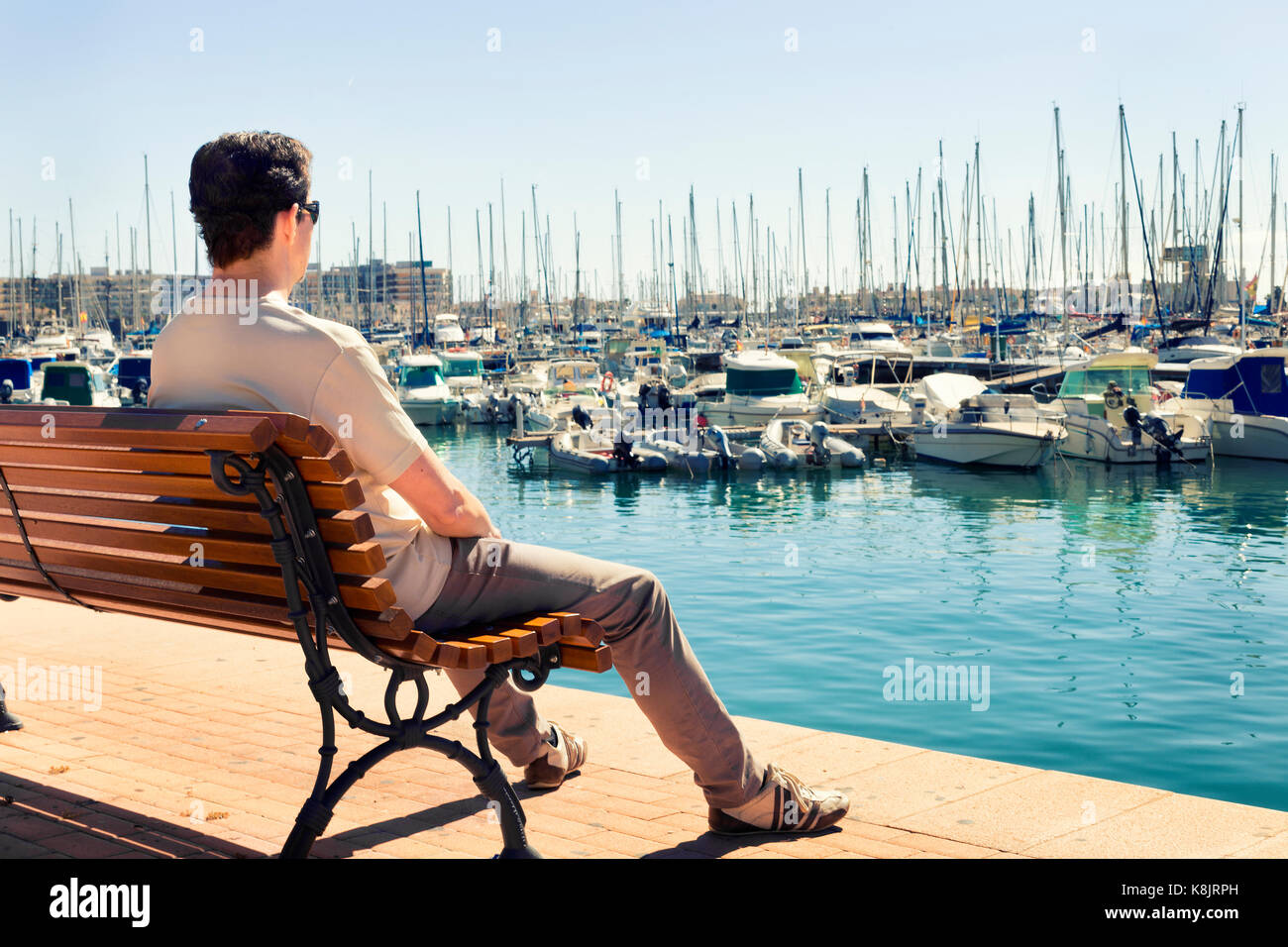 man sitting and  sunbathing on a bench contemplating the boats in the alicante port. Spain - Stock Image