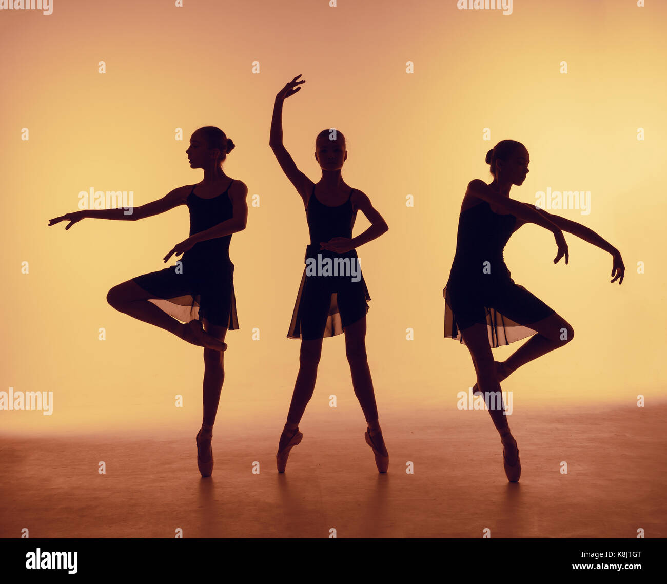 Composition From Silhouettes Of Three Young Dancers In Ballet Poses On A Orange Background