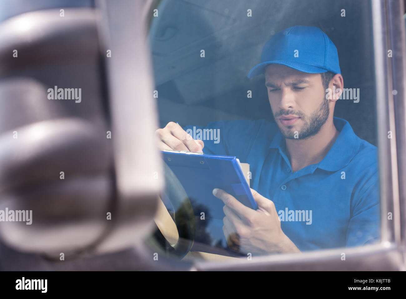 delivery man filling in documents - Stock Image