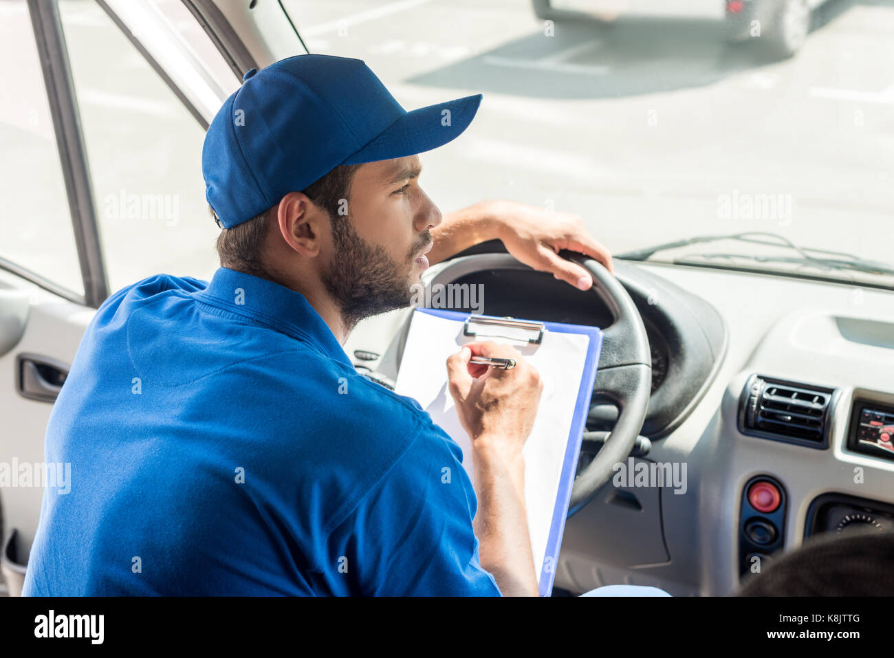delivery man writing on clipboard - Stock Image