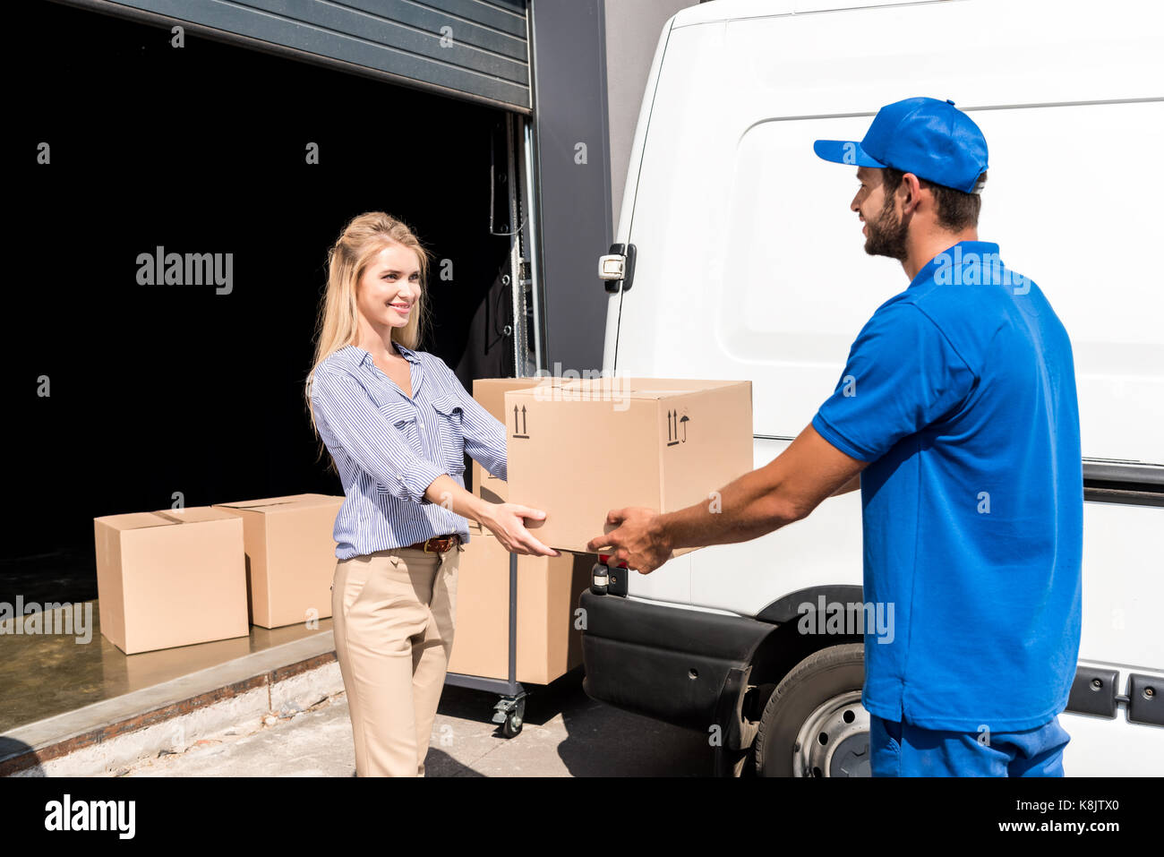courier giving package to woman - Stock Image