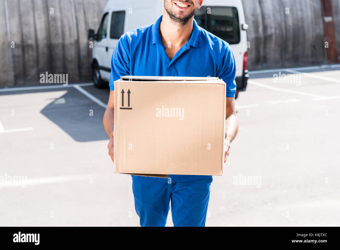 delivery man with cardboard box - Stock Image