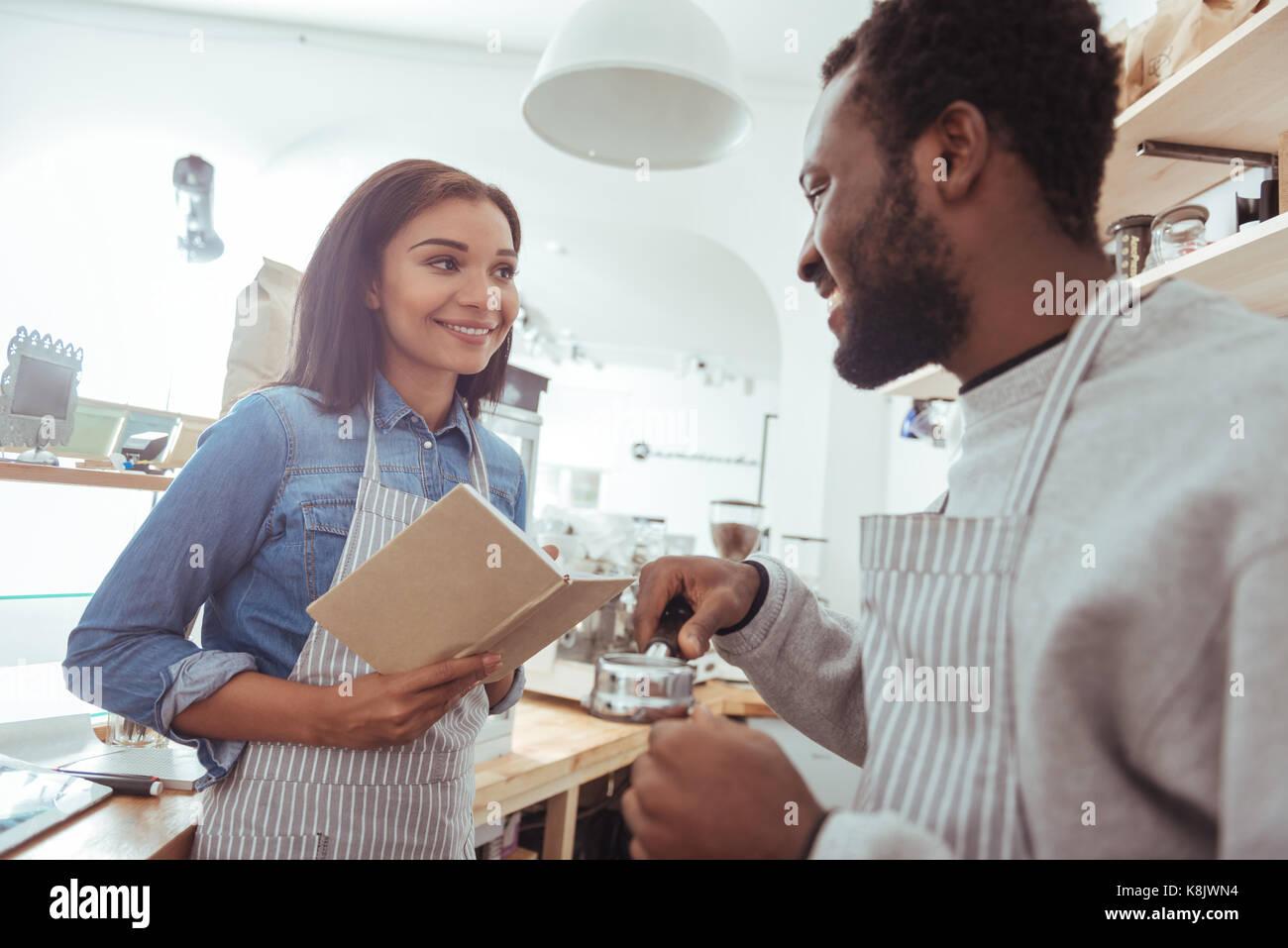 Charming barista explaining his colleague how to use portafilter - Stock Image