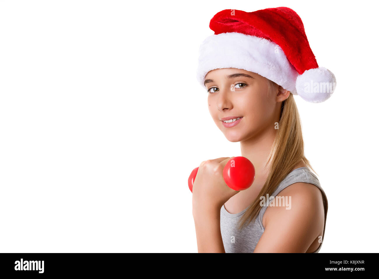Fitness christmas young girl training lifting hand weight wearing santa hat. Female model working out with dumbbells,isolated - Stock Image