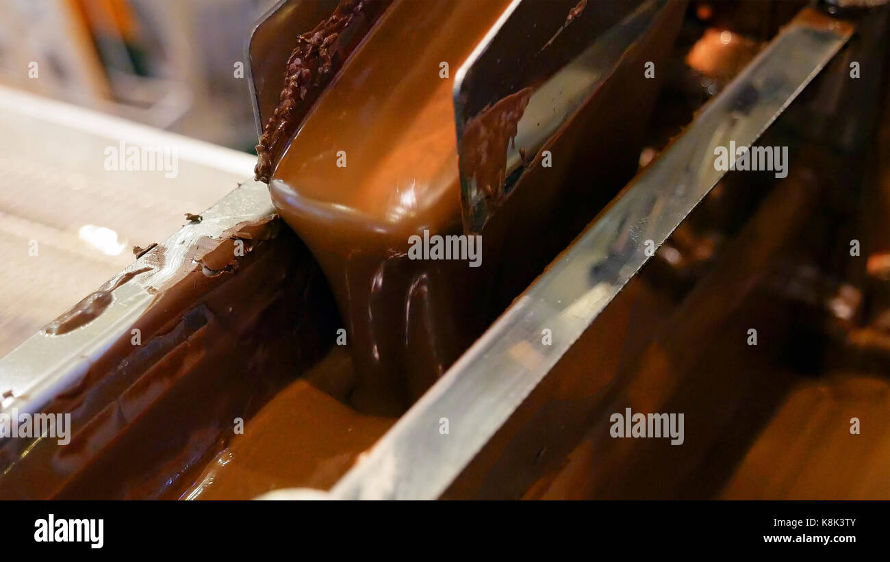 Liquid hot chocolate on the confectionery conveyor - Stock Image