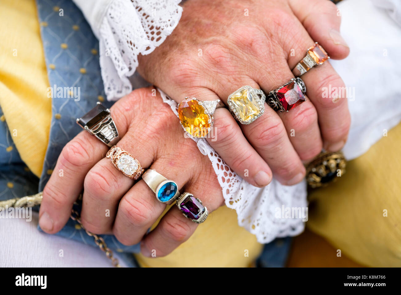 Crossed male hands with fingers adorned with multi-coloured semi-precious stone rings at a Renaissance Festival - Stock Image