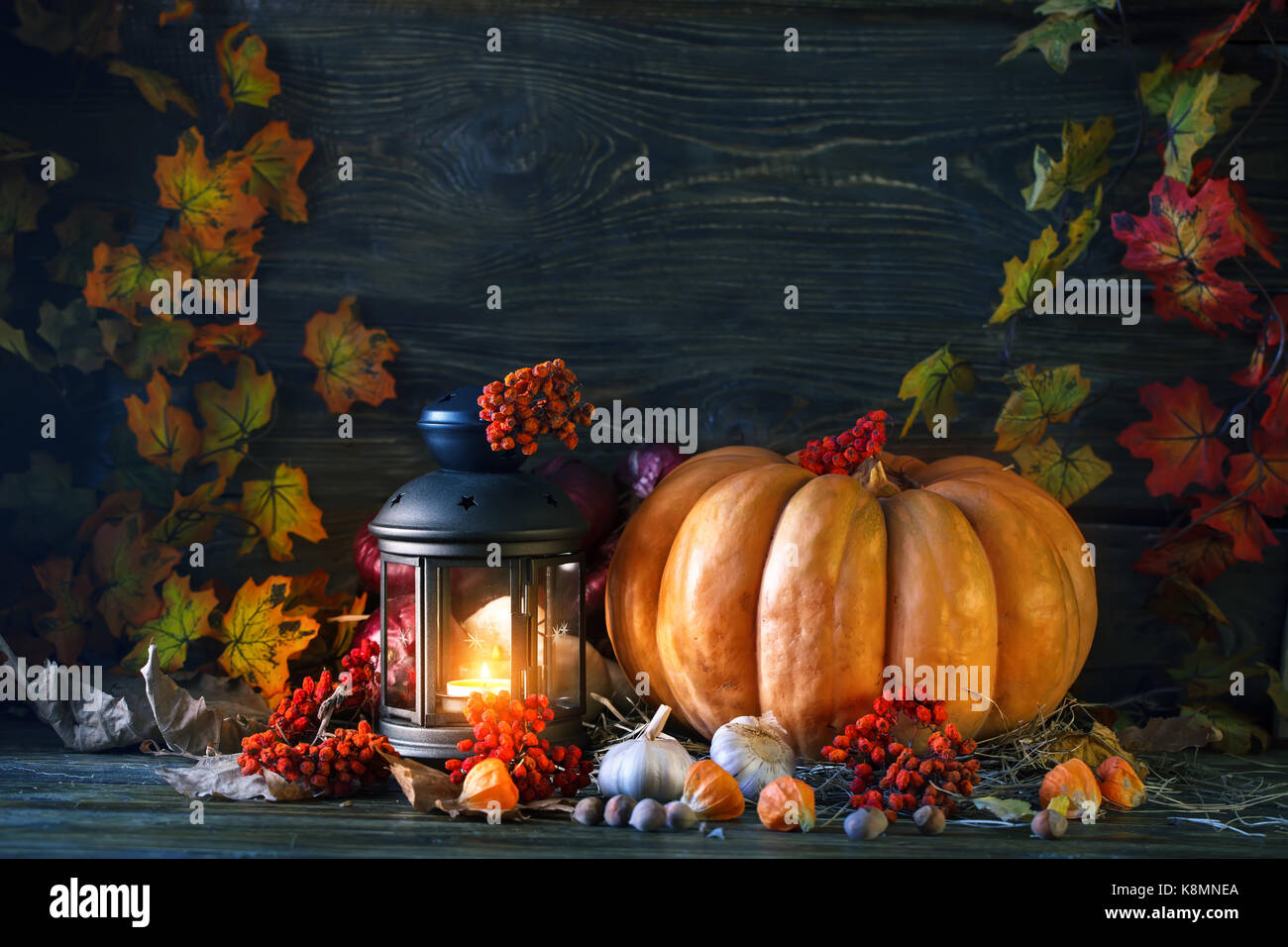 The wooden table decorated with vegetables, pumpkins and autumn leaves. Autumn background. Schastlivy von Thanksgiving - Stock Image