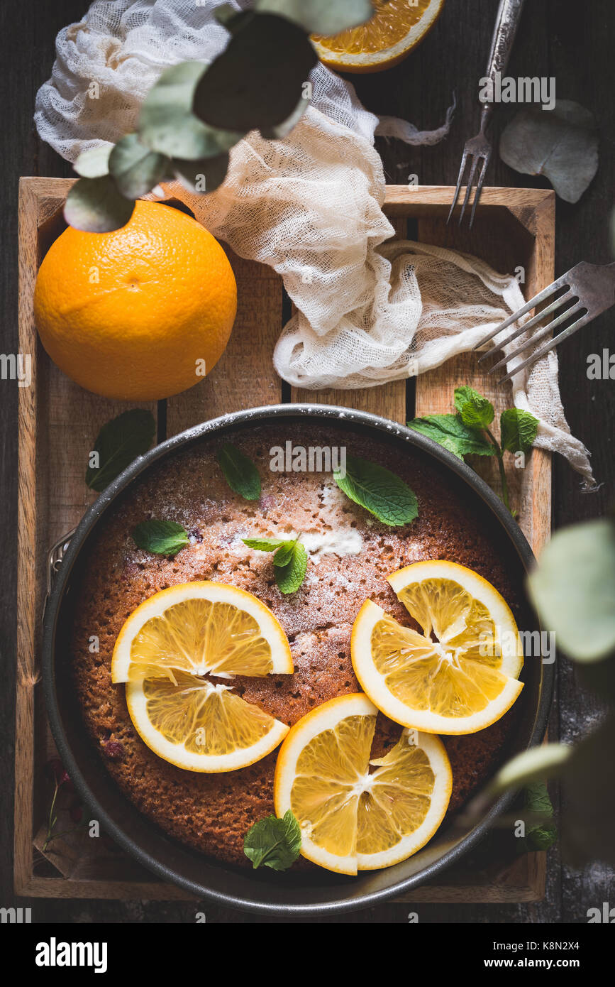 Orange cake decorated with orange slices and mint leaf on wooden tray. Top view. Food still life - Stock Image