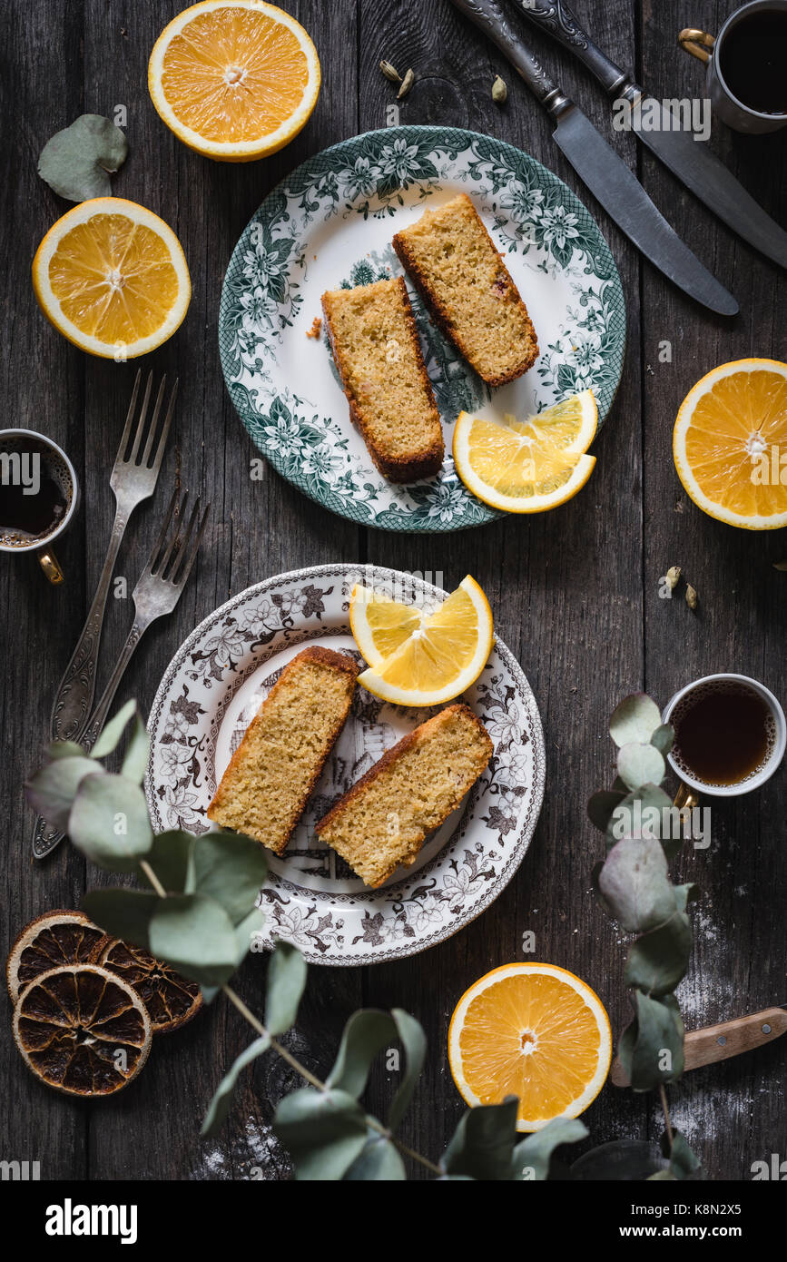 Orange cake served on vintage plates on rustic wooden table background. Food still life. Top view, vertical composition - Stock Image