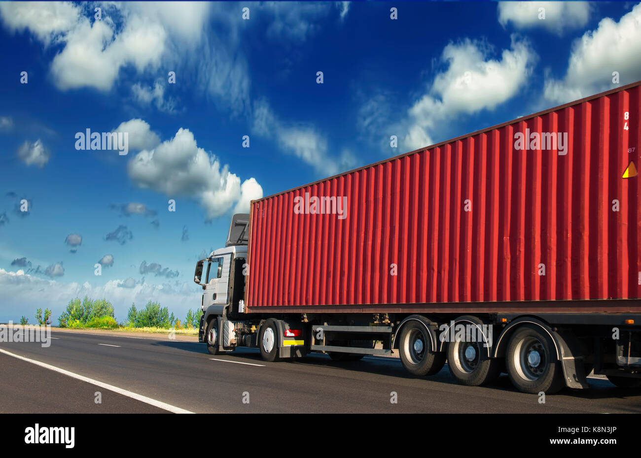 Trailers carrying containers clear day on the highway - Stock Image