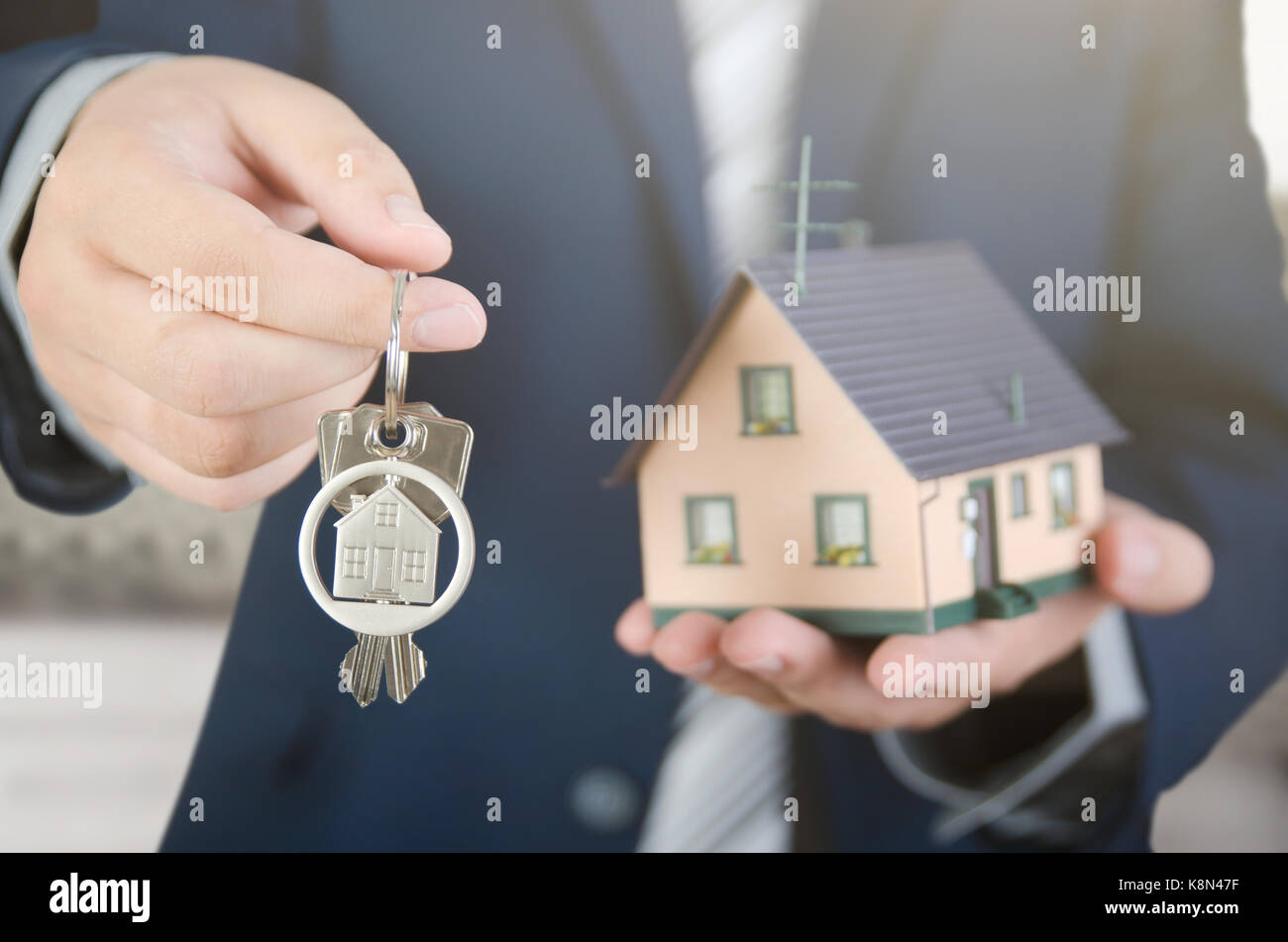 Real estate agent with home keys and house miniature. realestate key apartment real estate home house homeowner - Stock Image