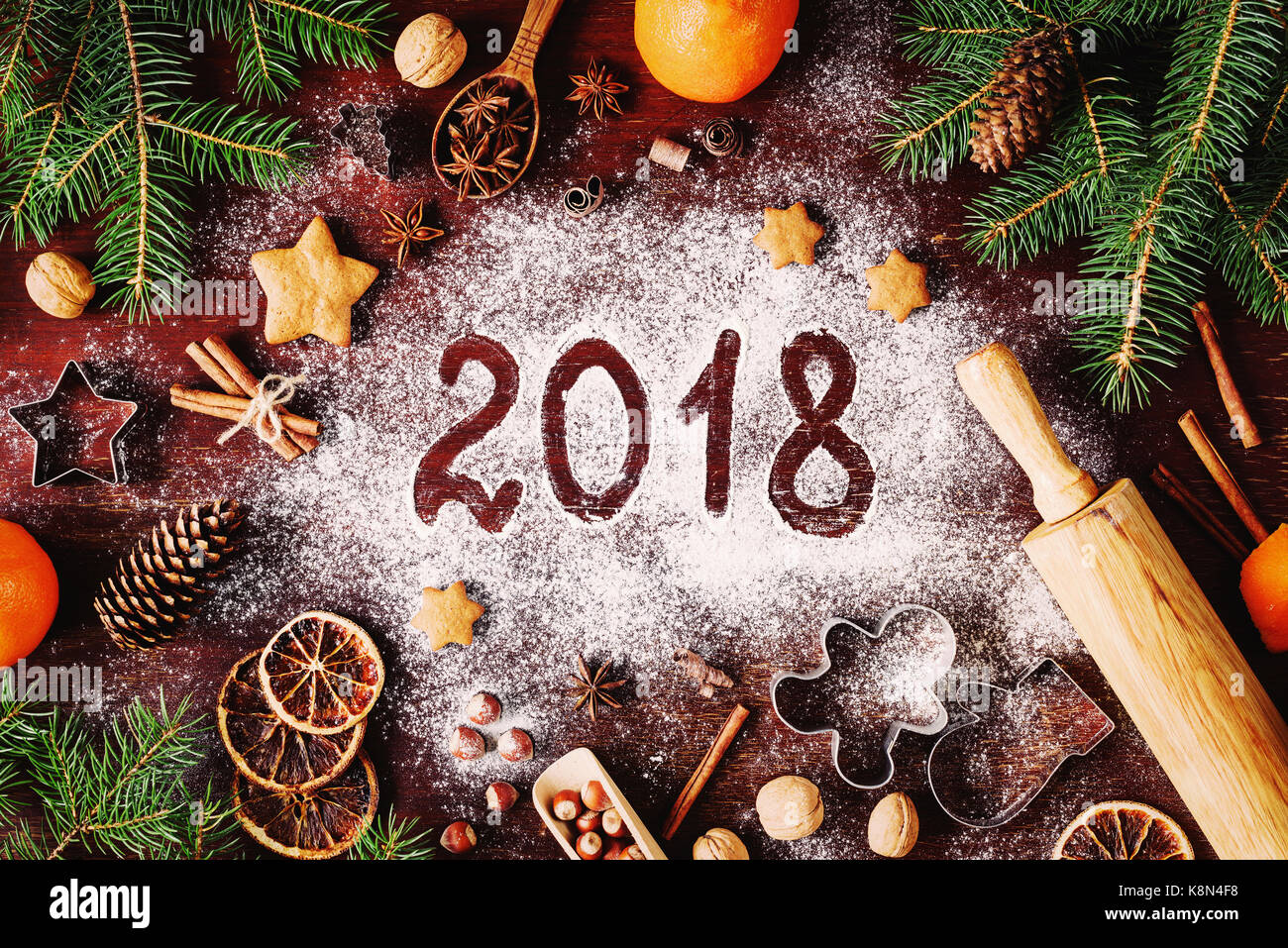 Happy New Year 2018 written on flour and Christmas Decorations Gingerbread cookies, cinnamin, oranges, spices, nuts - Stock Image