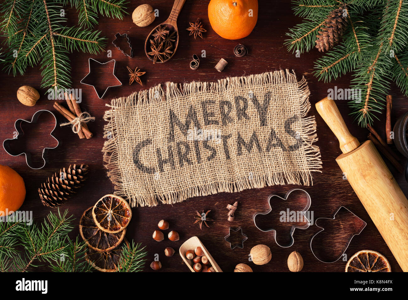 Merry Christmas greeting background with gingerbread cookies, spices, Christmas tree, oranges, nuts and Christmas - Stock Image