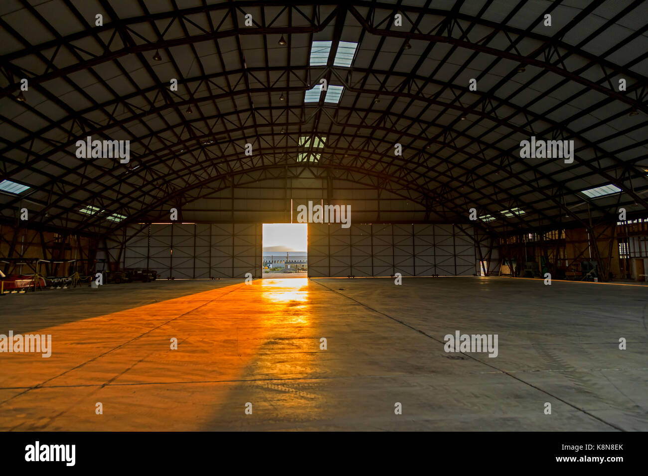 The setting sun shines through the front door into the interior of the Enola Gay Hangar at the Historic Wendover Stock Photo
