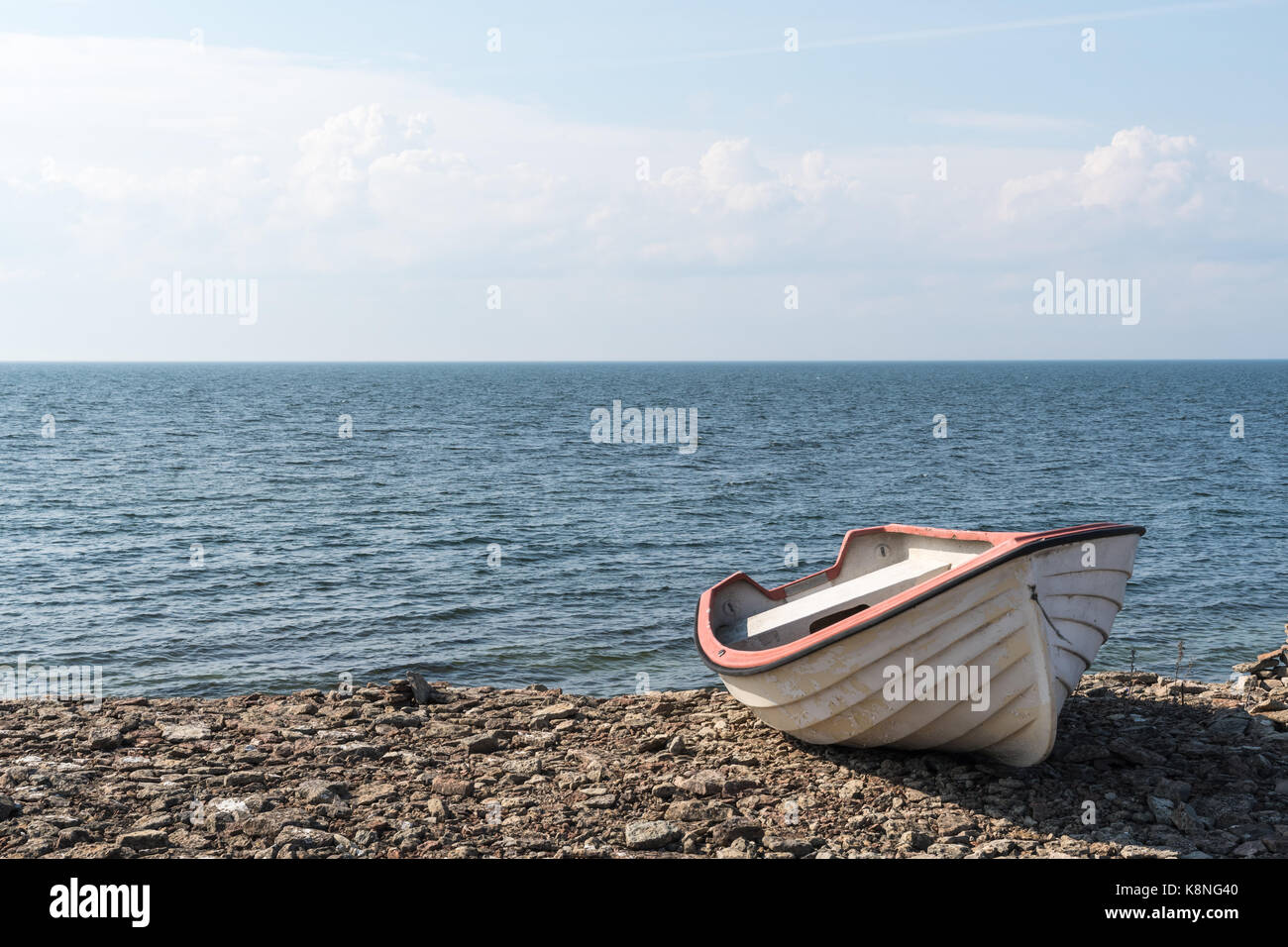 Small white rowing boat by a stony coast at the swedish island Oland - Stock Image