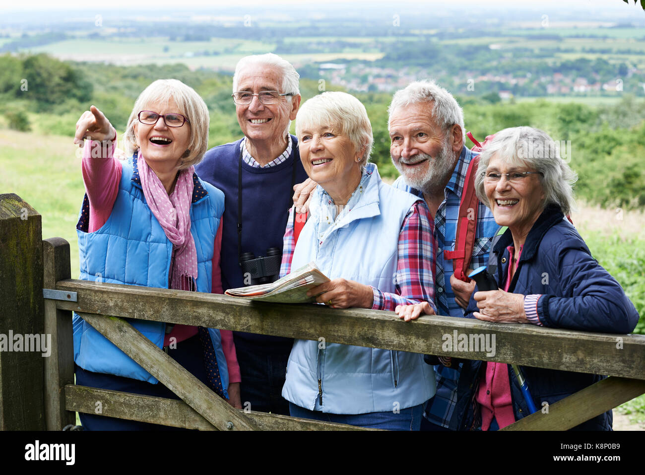 Group Of Senior Friends Hiking In Countryside - Stock Image