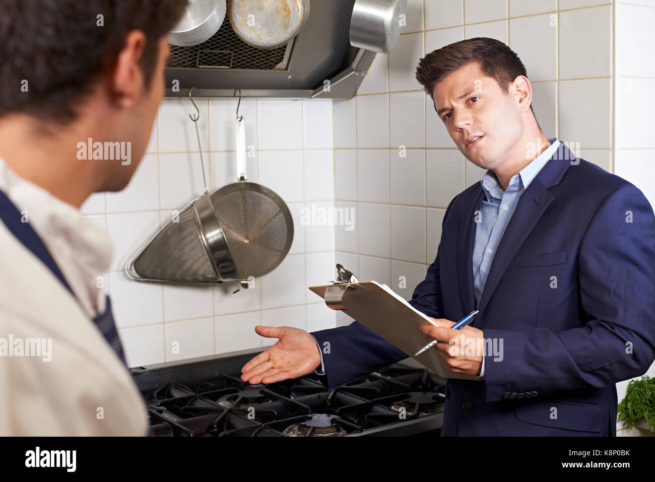 Health Inspector Meeting With Chef In Restaurant Kitchen - Stock Image
