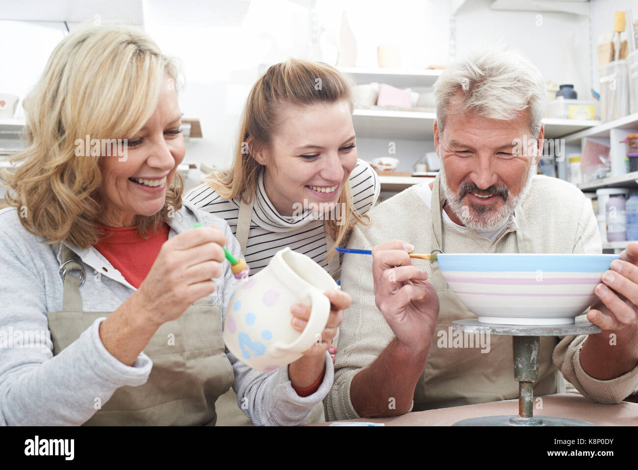 Mature Couple With Teacher In Pottery Class Stock Photo