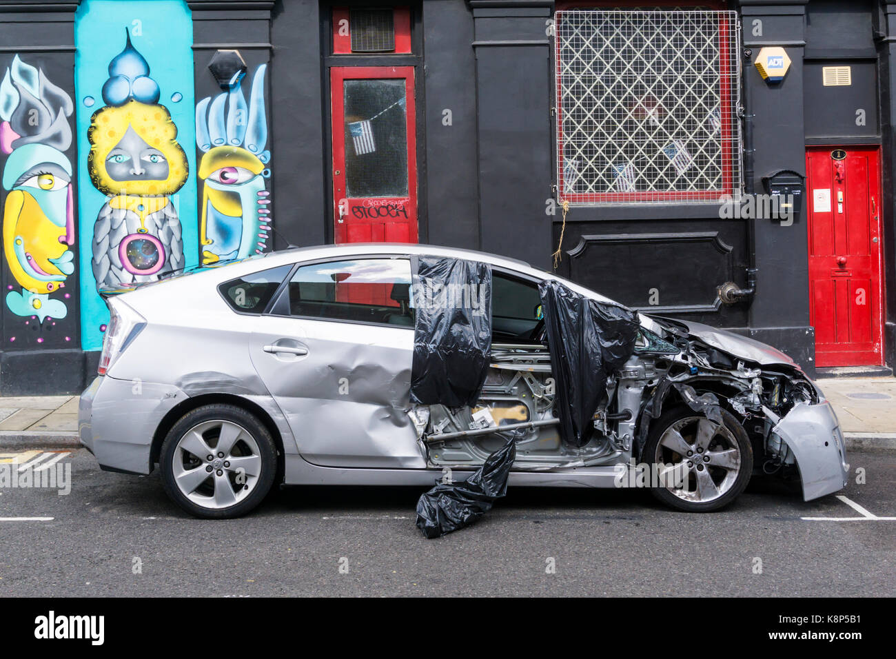 Damaged car left at side of city road after traffic accident. - Stock Image
