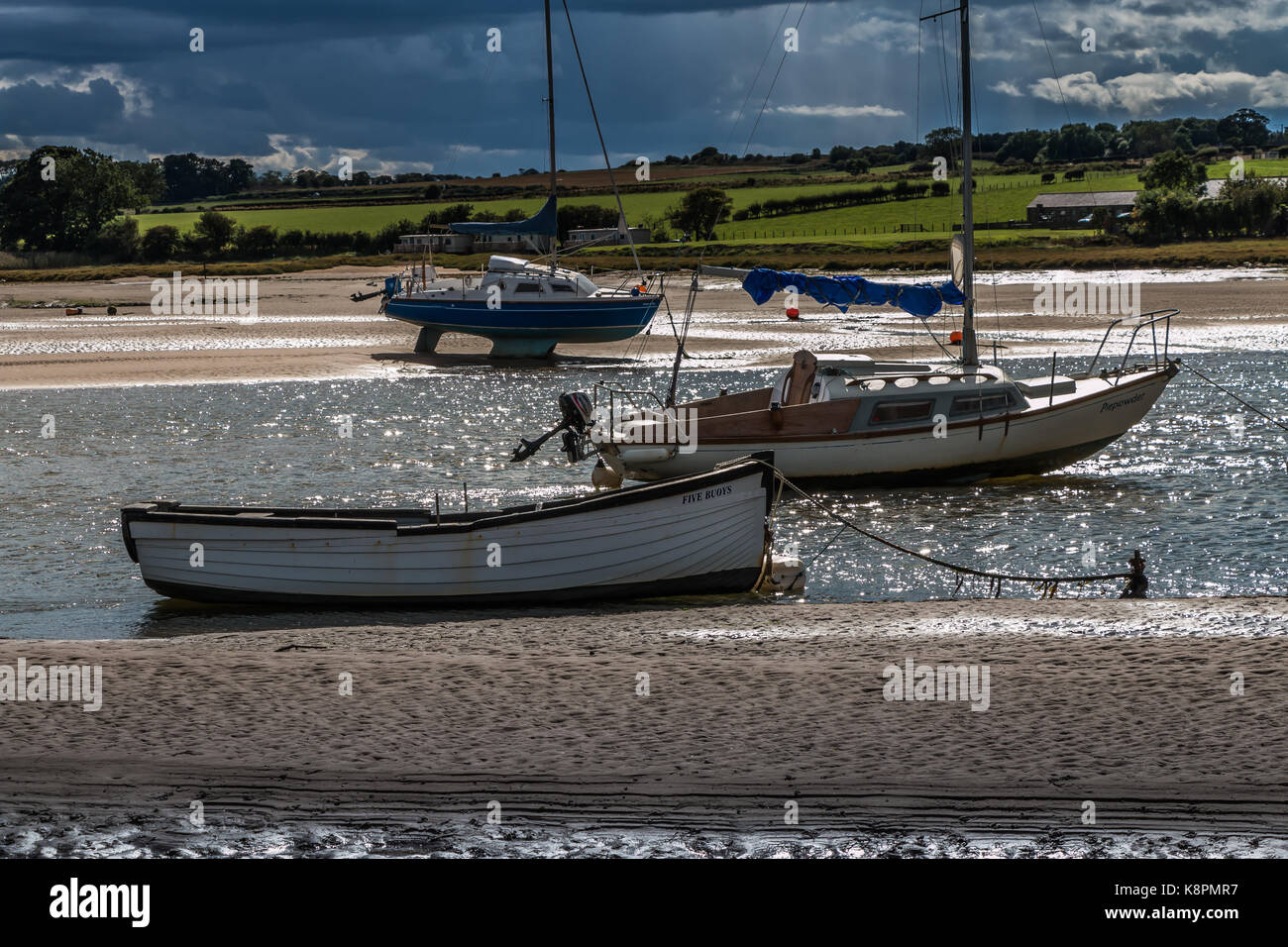 Northumberland coast, boats moored in Alnmouth Harbour, highlighthed by strong sunshine with a heavy squall approaching - Stock Image