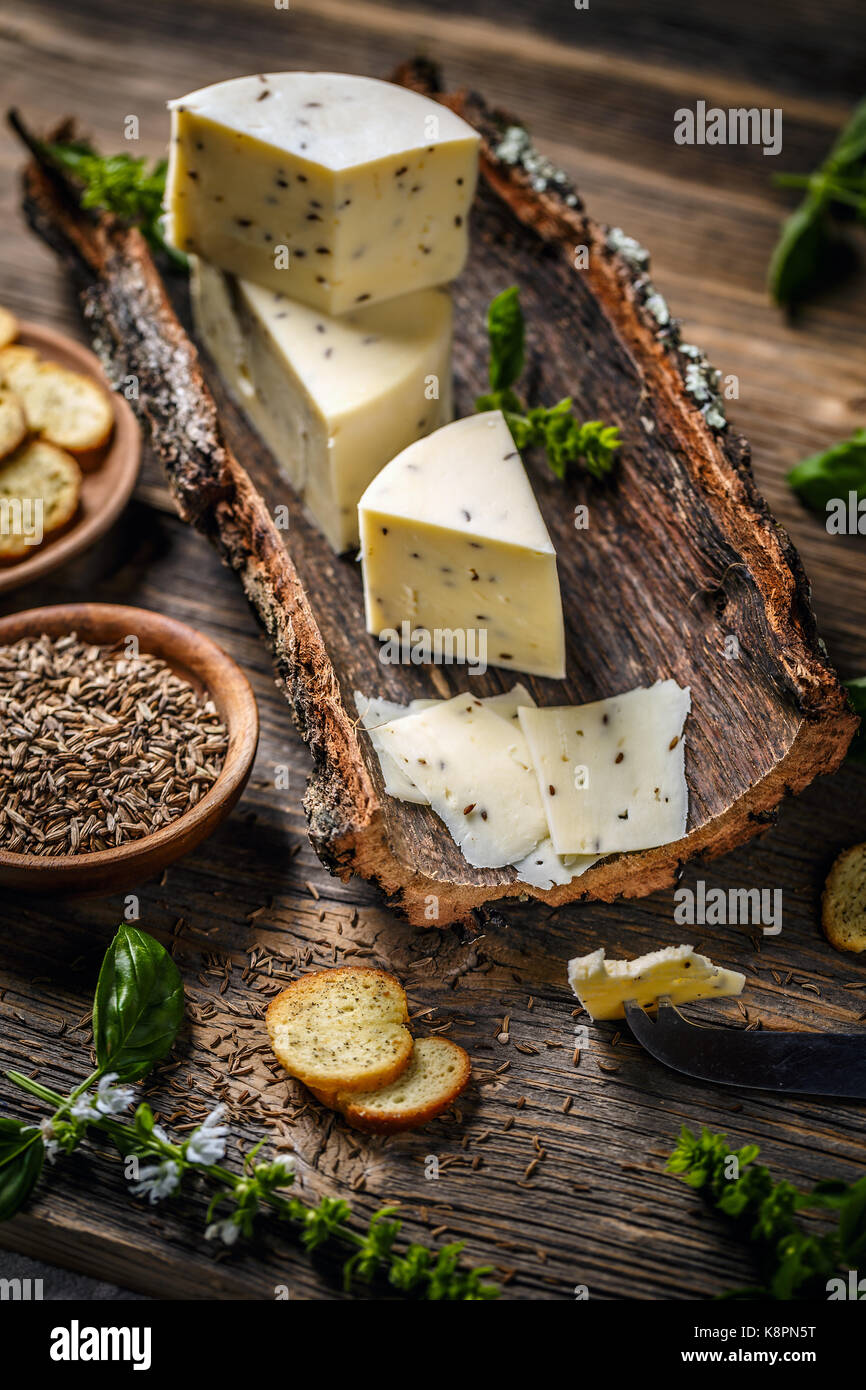 Still life of cheese on a bark with caraway seeds - Stock Image