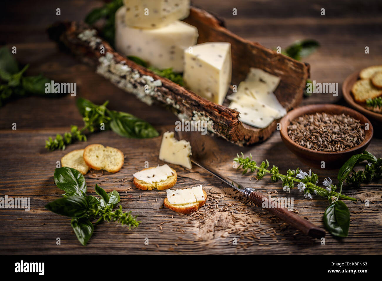 Still life of cheese with caraway seeds on bark - Stock Image