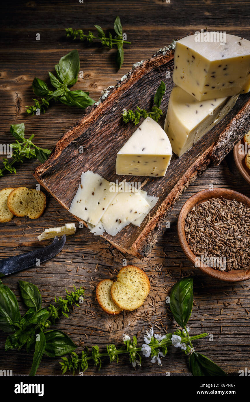 Cheese concept on a bark with caraway seeds - Stock Image