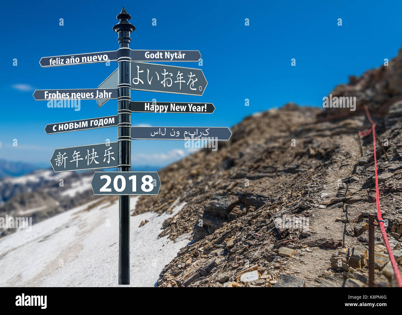 Signpost whit Happy New Year in many languages, mountain in background - Stock Image